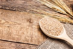 Wheat bran in wooden spoon with wheat ears Royalty Free Stock Photo
