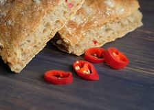 Wheat bread with chili pepper. On wooden background Stock Images