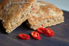 Wheat bread with chili pepper. On wooden background Stock Image