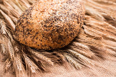 Wheat bread oblong on wheat spikelets. The properties are located on sackcloth. Royalty Free Stock Photo