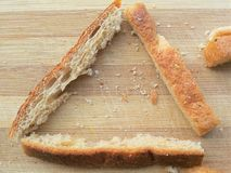 Wheat bread piece triangle on wooden background. Close up wheat bread piece triangle on wooden background stock image