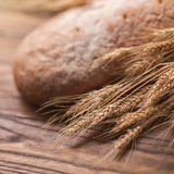 Wheat and bread on wooden table, shallow DOF Stock Photos