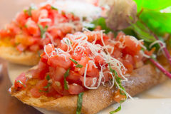 Wheat bruschetta with diced tomato salsa. Closeup view of wheat bruschetta with diced tomato salsa on a white plate with green leaves Royalty Free Stock Photo