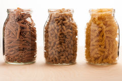 Wheat buckwheat and spelt pasta separated in three glass jars. Royalty Free Stock Photos