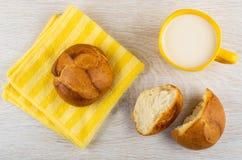 Wheat bun on napkin, cup of milk, broken bun on table. Top view stock photo