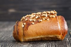 Wheat bun with nuts. On a wooden table, homemade cakes in the village stock images