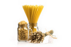 Wheat bunch, macaroni and pasta in jar, isolated on white background. Grain bouquet, golden spikelet. Stock Photography