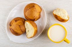 Wheat buns in plate, cup of milk, broken bun on table. Top view royalty free stock images
