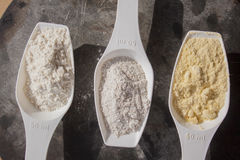 Wheat, corn and rye flour, on spoons. White wheat, yellow corn and grey rye flour, on spoons Stock Photos