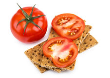 Wheat crisp bread and tomato isolated on white Royalty Free Stock Images