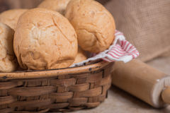 Wheat dinner rolls. Dinner rolls in a basket with burlap and a wooden roller in background Royalty Free Stock Images