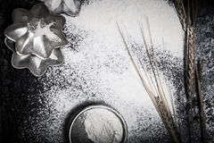 Wheat ears, baking forms, sieve and sprinkle flour on black back Stock Photos