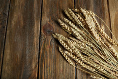 Wheat ears on brown wooden background Stock Images