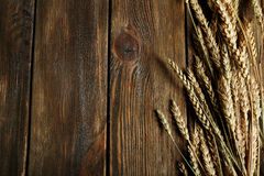 Wheat ears on brown wooden background Stock Photo