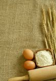 Wheat ears, flour and eggs on sacking. Stock Photo