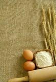 Wheat ears, flour and eggs on sacking. Stock Photo