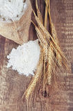 Wheat ears and flour sack on wooden background Royalty Free Stock Photos