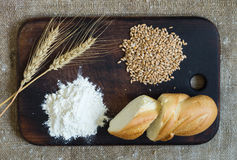 Wheat ears, grains, flour and sliced bread on a kitchen board on a sacking background Stock Image