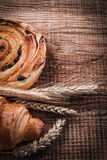 Wheat ears raisin roll tasty croissant on oak wooden board food stock images