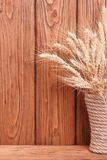 Wheat ears in a vase on a wooden boards Stock Images