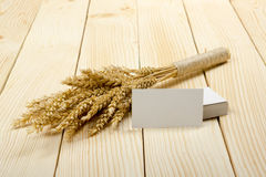 Wheat Ears on Wooden Table with blank business cards. Sheaf of Wheat over Wood Background. Harvest concept. Stock Photo