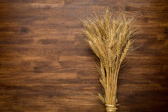 Wheat Ears on the Wooden Table. Sheaf of Wheat stock images
