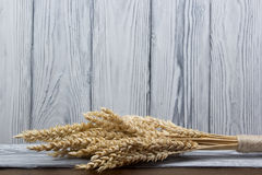 Wheat Ears on Wooden Table. Sheaf of Wheat over Wood Background. Harvest concept. Stock Photo