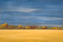 Wheat field. Landscape background field in the foreground, autumnal trees in the middle ground and a blue sky Royalty Free Stock Images