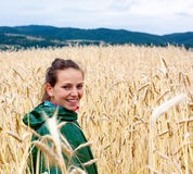 Wheat field. Young woman with a rain coat walkig through wheat field Royalty Free Stock Image