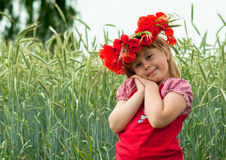 Wheat field. The smiling little girl with a wreath from poppies, costs in a wheaten field Royalty Free Stock Photo
