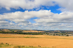 Wheat field and blue sky with clouds at shore line. Close to North sea, Aberdeen, Scotland, UK Royalty Free Stock Image