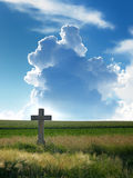 Wheat field with cross and cloudy sky. Blue sky with big cloud, green field with stone cross Royalty Free Stock Photos