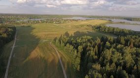 Aerial view of a village on the banks of a large lake in the distance. With a wheat field and forest below, one can see a village in the distance on the banks of stock video footage