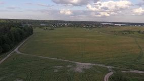 Aerial view of a village on the banks of a large lake in the distance. With a wheat field and forest below, one can see a village in the distance on the banks of stock footage