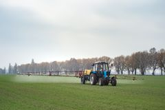 Wheat field tractor spraying agrochemical or agrichemical over y. Oung grain field in most cases agrichemical refers to pesticides like insecticides herbicides Royalty Free Stock Images