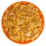 Sunshiny orange bowl of breakfast cereal cornflakes, isolated. Wheat flakes in orange bowl. White background Royalty Free Stock Photo
