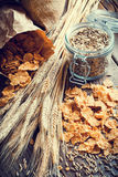 Wheat flakes, spikes and rye grain on wooden table Royalty Free Stock Image