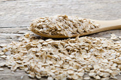 Wheat flakes a wooden spoon on the table Royalty Free Stock Photography