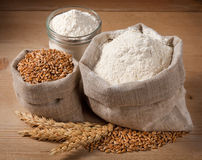 Wheat and flour in the bag, jar on the boards. Spikelets Stock Image