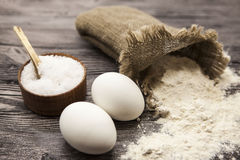 Wheat flour in a canvas bag, a large salt shaker wood, raw eggs: set for making homemade bread dough on a beautiful dark wooden ba Royalty Free Stock Images