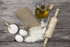 Wheat flour in a canvas bag, the olive oil in a glass carafe, a large salt shaker wood, raw eggs, a wooden rolling pin: set for ma Royalty Free Stock Photos