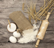 Wheat flour in a canvas bag, with spikelets of rye, a large salt shaker wood, raw eggs, a wooden rolling pin: set for making homem. Ade bread dough on a Stock Photography
