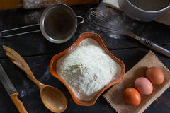 Wheat flour in a ceramic dish and chicken eggs for the dough preparation Royalty Free Stock Images