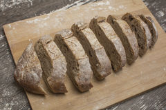 Wheat flour with a fresh bread cutted into slices. On the table Royalty Free Stock Photography