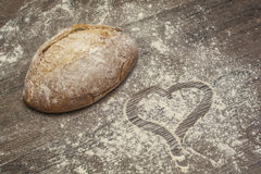 Wheat flour with a fresh bread and shape of heart. On the table Royalty Free Stock Photography