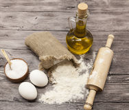 Wheat Flour In A Canvas Bag, The Olive Oil In A Glass Carafe, A Large Salt Shaker Wood, Raw Eggs, A Wooden Rolling Pin: Set For Ma Stock Photo