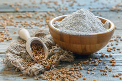Wheat flour and scoop with the grain. Whole-wheat flour from wheat in a bowl and scoop with the grain on an old wooden table Stock Photography