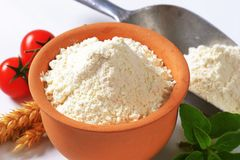 Wheat flour in terracotta dish and metal scoop Stock Photography