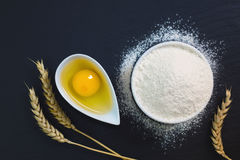 Wheat flour in white cup and organic egg decorate by wheat ear on black slate stone plate with copy space Royalty Free Stock Photography