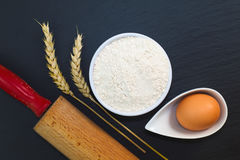 Wheat flour in white cup and organic egg decorate by wheat ear, rolling pin on black slate stone plate with copy space Royalty Free Stock Photo